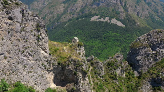 vídeos de stock e filmes b-roll de aerial: drone approaching house on cliff by small village - alpes-maritimes, france - alpes europeus