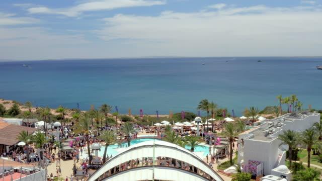 stockvideo's en b-roll-footage met aerial: drone approaching people at tourist resort against sea and sky - ibiza, spain - verblijfsoord
