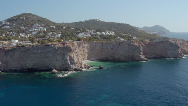 aerial: drone approaching rock formations by sea - ibiza, spain - coastal feature stock videos & royalty-free footage
