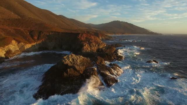 vídeos y material grabado en eventos de stock de aerial: drone approaching rocky coastline while waves splashing in sea at beach during sunset, scenic view of mountains against sky - big sur, california - cresta montaña