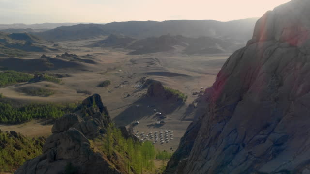 aerial: drone approaching small village with traditional yurts by rocky mountains during sunny day - ulaanbaatar, mongolia - ulan bator stock videos & royalty-free footage