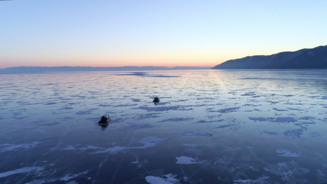 Aerial: Drone approaching towards hovercrafts traveling on icy Lake Baikal
