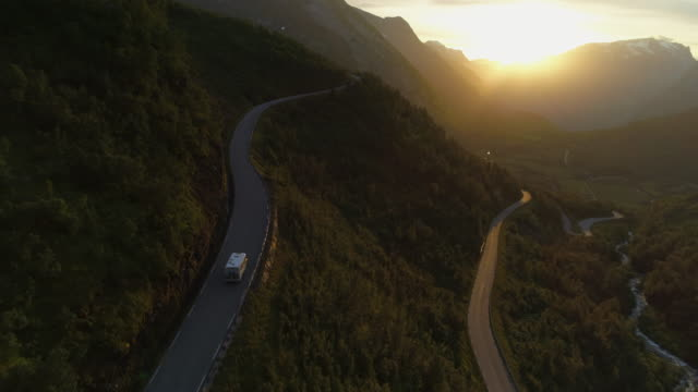 aerial: drone approaching towards motor home traveling on winding road over mountains during sunset - geiranger fjord, norway - mountain road stock videos & royalty-free footage