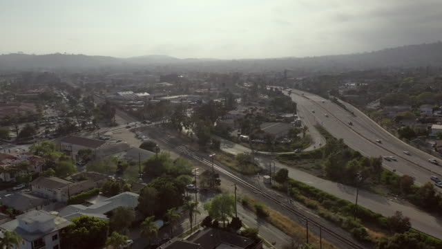 aerial: drone approaching vehicles moving on roads amidst buildings in city against sky during morning - santa barbara, california - santa barbara bildbanksvideor och videomaterial från bakom kulisserna