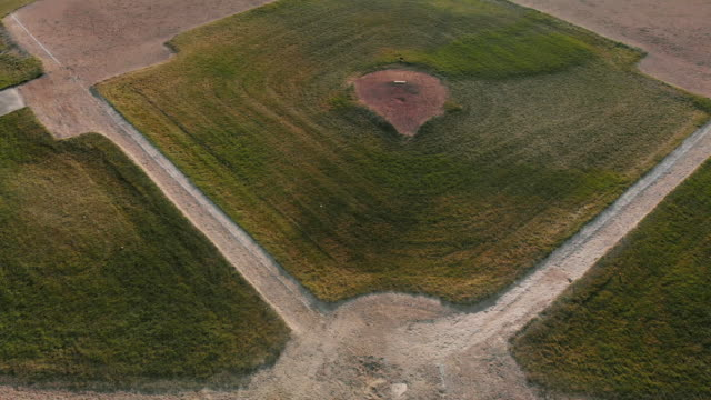 aerial drone camera tilts down to reveal home base of an empty baseball diamond/field at sunset/sunrise - baseball diamond stock videos and b-roll footage