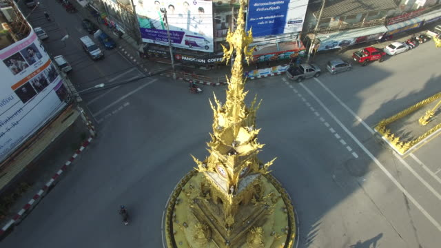 aerial drone circle of the golden clock tower sitting in the middle of a roundabout on baanpa pragarn road in central chiang rai - clock tower stock videos & royalty-free footage