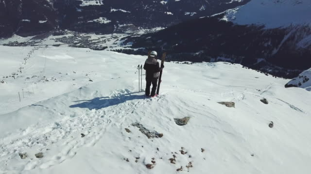 vídeos de stock, filmes e b-roll de aerial drone circling view of a skier with skis on top of a snow covered mountains in the winter. - orbitando