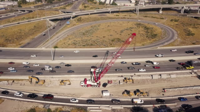 aerial drone clip looking down on i-15, i-80 of the commuter traffic and road construction around salt lake city - roadworks stock videos & royalty-free footage