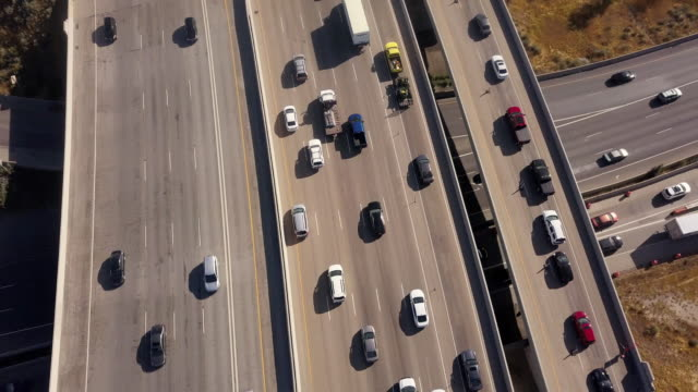 aerial drone clip looking down on i-15, i-80 of the commuter traffic and train in salt lake city - major road stock videos & royalty-free footage