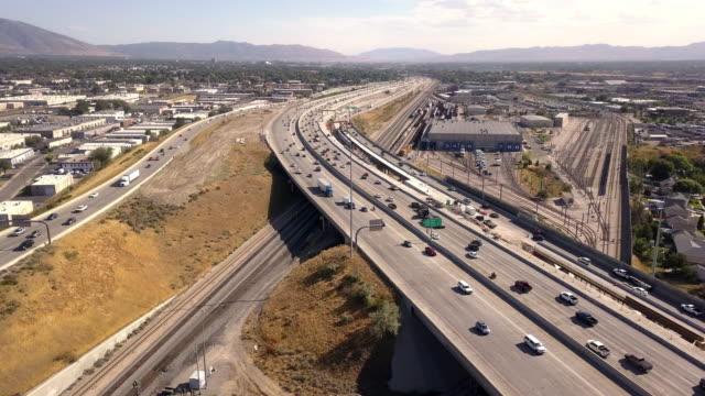 aerial drone clip looking down on i-15, i-80 of the commuter traffic and road construction around salt lake city - motorway stock videos & royalty-free footage