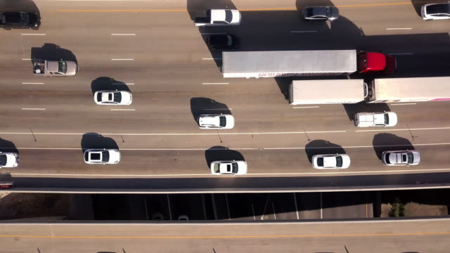 aerial drone clip looking down on i-15, i-80 of the commuter traffic and train in salt lake city - heavy goods vehicle stock videos & royalty-free footage