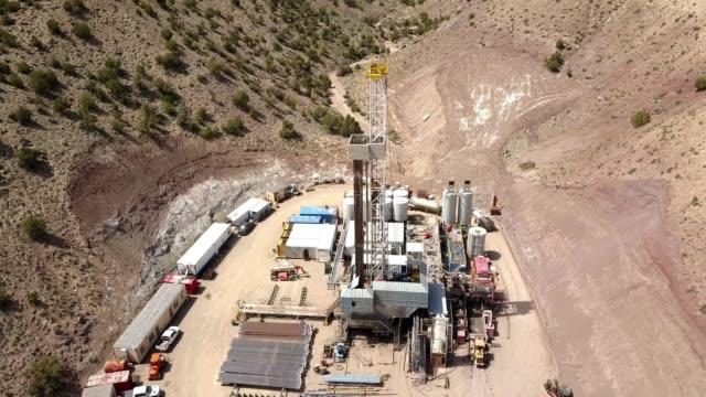 vídeos de stock, filmes e b-roll de grampo aéreo do zangão de um equipamento de broca do fracking nos montes de colorado na primavera - boca de poço