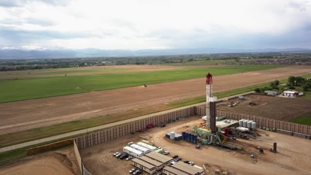 vídeos de stock, filmes e b-roll de grampo aéreo do zangão de um equipamento de broca do fracking na inclinação oriental de colorado na primavera atrasada - boca de poço