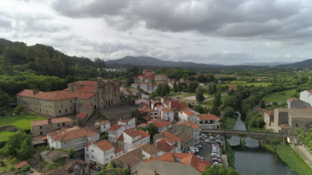 aerial: drone descending over bridge on sar river amidst buildings in town against cloudy sky - padron, spain - 女子修道院点の映像素材/bロール