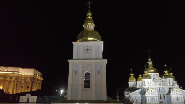 vídeos de stock e filmes b-roll de aerial drone establishing shot flying over mykhailivs'ka square towards st michael's golden domed monastery at night in kiev ukraine - aerial or drone pov or scenics or nature or cityscape