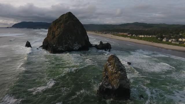 aerial drone establishing shot of cannon beach haystack rock sea stack and coastline - oregon coast stock videos & royalty-free footage