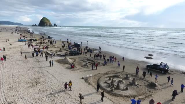 aerial drone establishing shot of oregon sandcastle contest crowd and sandcastles on coastline of cannon beach - oregon coast stock videos & royalty-free footage