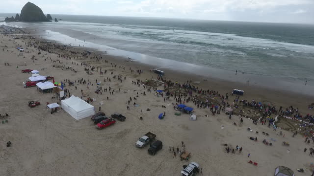 aerial drone establishing shot of oregon sandcastle contest crowd gathering around sandcastles on coastline of cannon beach - oregon coast stock videos & royalty-free footage