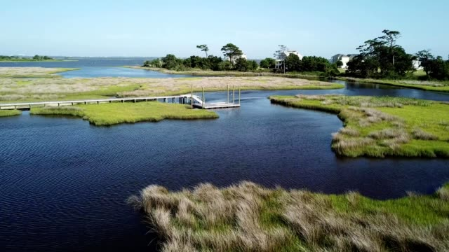 aerial drone flight over a marsh grass off the waters of an intracoastal waterway in emerald isle north carolina - inlet stock videos & royalty-free footage