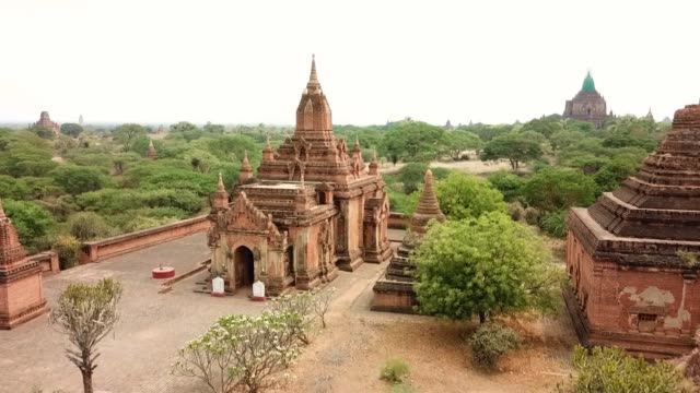 vidéos et rushes de aerial: drone flying forward towards buddhist temple amidst trees against clear sky - bagan, myanmar - temple