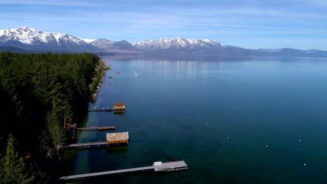 vidéos et rushes de drone aérien survolant les quais s'étendant dans les eaux bleues cristallines de lake tahoe, californie - sierra nevada californienne