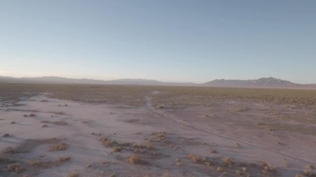 aerial drone flyover of an isolated desert road in rachel nevada - ネバダ州点の映像素材/bロール