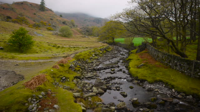aerial drone footage flying up a stream in the lake district - english lake district stock videos and b-roll footage