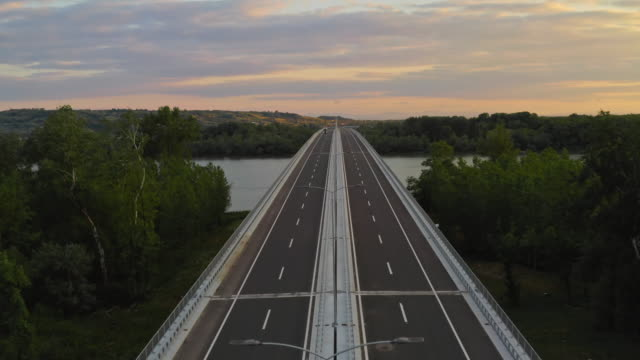 aerial drone footage: long haul semi truck driving on the empty highway across bridge. landscape and river in the background - empty road stock videos & royalty-free footage