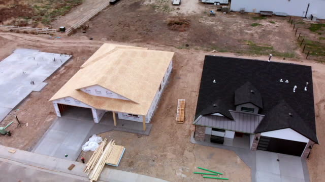 aerial drone footage of a new subdivision with houses and homes under construction - incomplete stock videos & royalty-free footage
