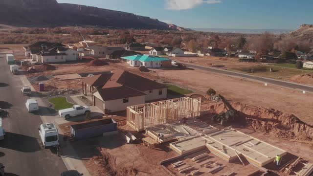 aerial drone footage of a residential wood-framed building site in an upscale western colorado neighborhood near fruita with completed homes and others still under construction - incomplete stock videos & royalty-free footage
