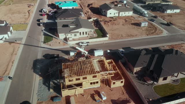 aerial drone footage of a residential wood-framed building site in an upscale western colorado neighborhood near fruita with completed homes and others still under construction - detached stock videos & royalty-free footage
