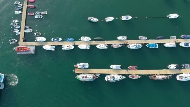 aerial drone footage of boats docked in a marina in the clear blue water of the river dart in the town of dartmouth, devon, uk. - marina stock videos & royalty-free footage