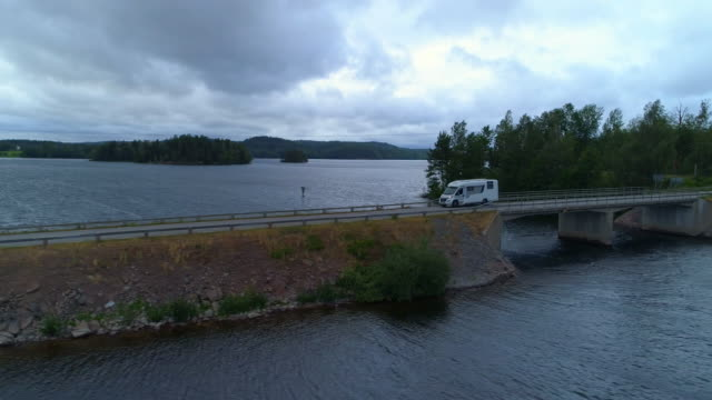 aerial: drone footage of camper van moving on bridge connecting road over lake - asunden, sweden - camper van stock videos & royalty-free footage