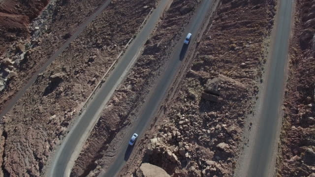 Aerial drone footage of cars moving on road amidst arid landscape
