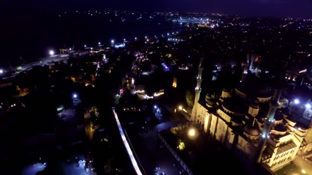 Aerial drone footage of illuminated Blue Mosque and cityscape at night