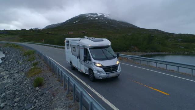 aerial: drone footage of motor home drives on highway amidst beautiful lake - breiddalsvatnet, norway - camper van stock videos & royalty-free footage