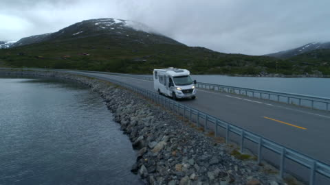 aerial: drone footage of motor home drives on highway amidst lake during sunset - breiddalsvatnet, norway - coastal feature stock videos & royalty-free footage