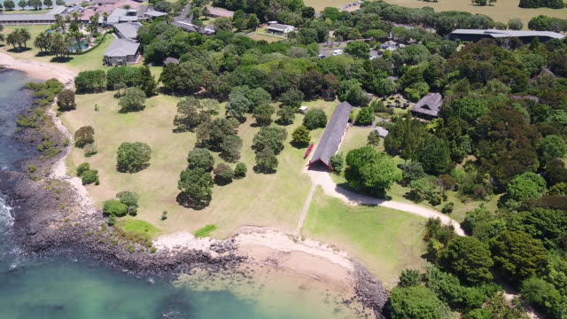 aerial drone footage of ngatokimatawhaorua waka house at waitangi treaty grounds bay of islands new zealand - baia delle isole nuova zelanda video stock e b–roll