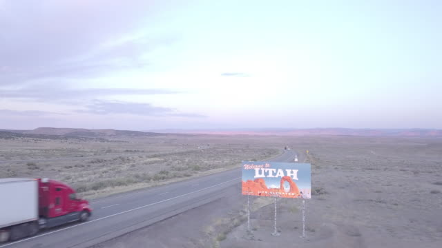 aerial drone footage of semi-trucks passing utah state line - convoy trucks stock videos and b-roll footage