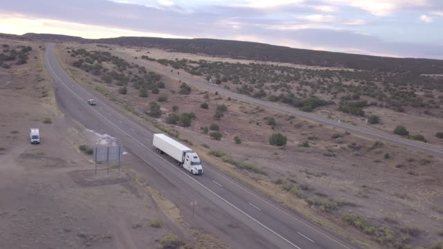 aerial drone footage of semi-trucks rolling down the highway - convoy stock videos and b-roll footage