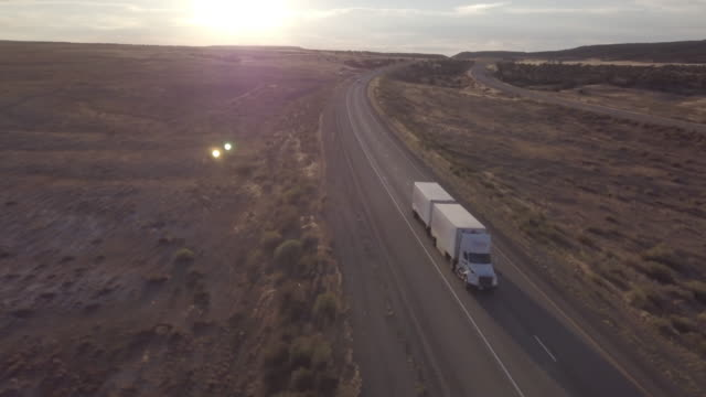 aerial drone footage of semi-trucks rolling down the highway - convoy trucks stock videos and b-roll footage