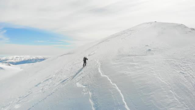vídeos y material grabado en eventos de stock de imágenes de drones aéreos de escalador alpino de montaña en pico de montaña de gran altitud en invierno - nevosa