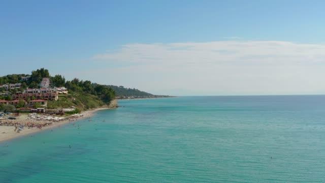 vidéos et rushes de images aériennes de drone du village de bord de mer et de skala (plage) de fourka dans kassandra, chalkidiki, halkidiki, mer egée, grèce, en été - grèce