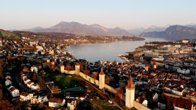 aerial drone footage of the sunset over luzern old town fortification - 要塞点の映像素材/bロール