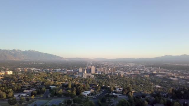 夏の夕暮れ時のユタ州議会議事堂と周辺のダウンタウンの高層ビルと住宅の空中ドローン映像 - 新古典派点の映像素材/bロール