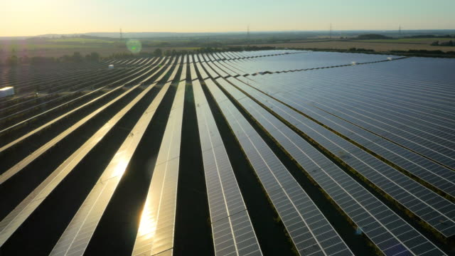 Aerial drone footage of UK solar panel farm at sunset with lens-flares