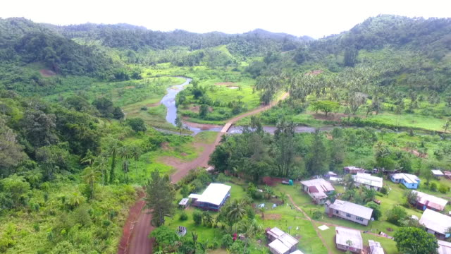 aerial drone footage of village of naviavia in fiji with homes bush area and river in the distance - isole del pacifico video stock e b–roll