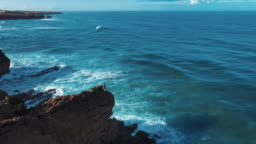 Aerial Drone Footage: Portuguese Rocky Shore with Beautiful Ocean View. Flying Over Portugal, Coastline with Oceanic Waves Rolling, Crashing into Cliffs. Lonely Fisherman is Fishing. Praia Do Guincho