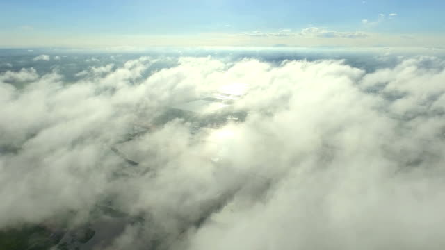 Aerial Drone Footage View:Scenic flight above the clouds towards the sun