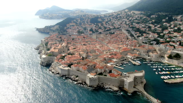 aerial drone footage walls of dubrovnik red-roofed city, croatia - croazia video stock e b–roll